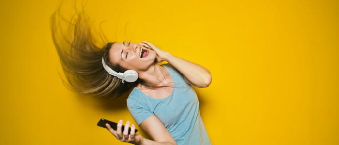 Frau mit Handy und Kopfhörern